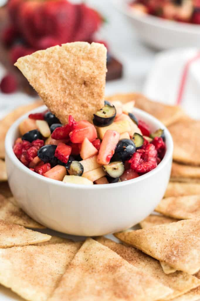 a white bowl full of fruit salsa with a cinnamon chip sticking out of it