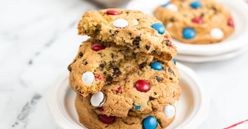 A stack of M&M cookies on a white plate.
