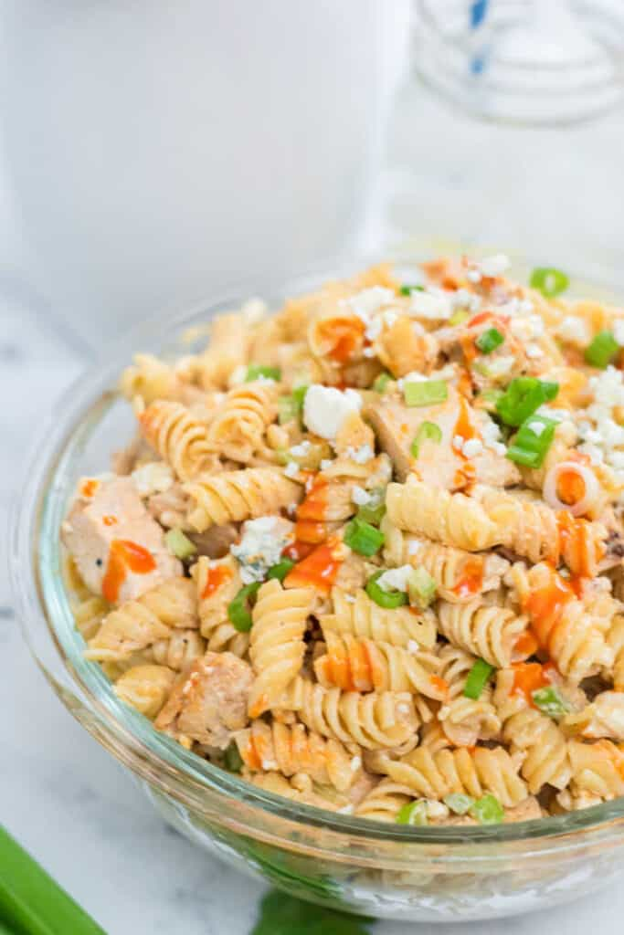 A large glass bowl full of buffalo chicken pasta salad