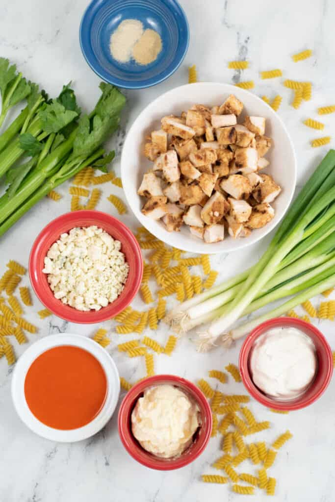 The ingredients for buffalo chicken pasta salad bowls containing chopped chicken buffalo sauce, blue cheese, mayonnaise and sour cream. There are green onions, stalks of celery and uncooked noodles sprinkled around the bowls