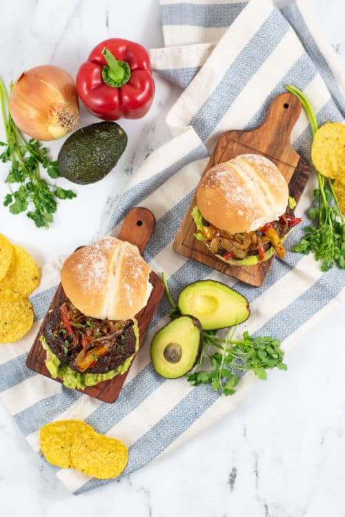 two burgers on wooden boards surrounded by fresh veggies
