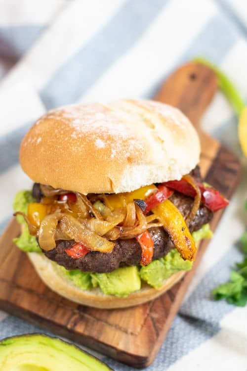 a burger on a bun with guacamole peppers and onions