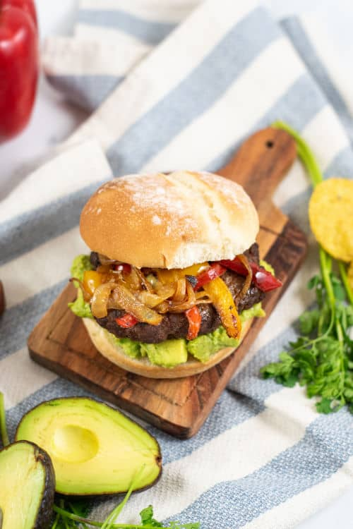 A fajita burger topped with peppers and onions on a wood plank