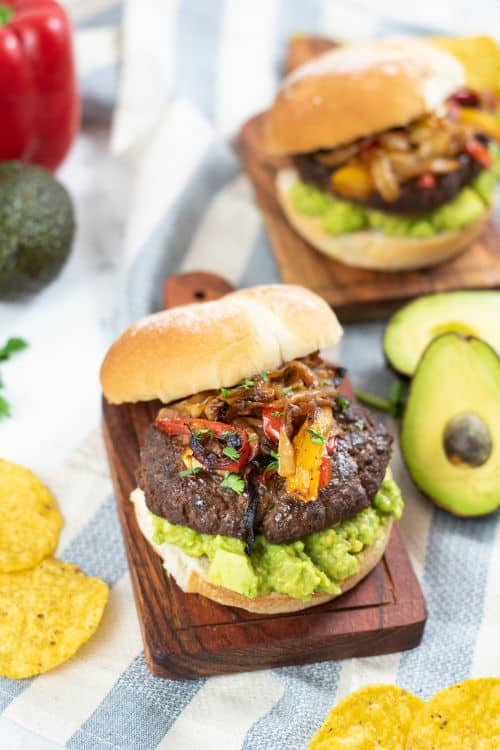 A fajita burger on guacamole topped with onions and peppers