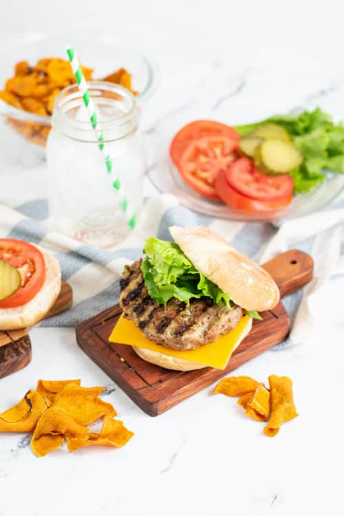 A turkey zucchini burger on a wooden plate topped with lettuce and cheese. Behind it is a plate of burger toppings, a mason jar full of water and a bowl of chips