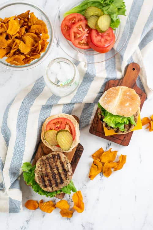 A table set with burgers, chips and burger toppings.
