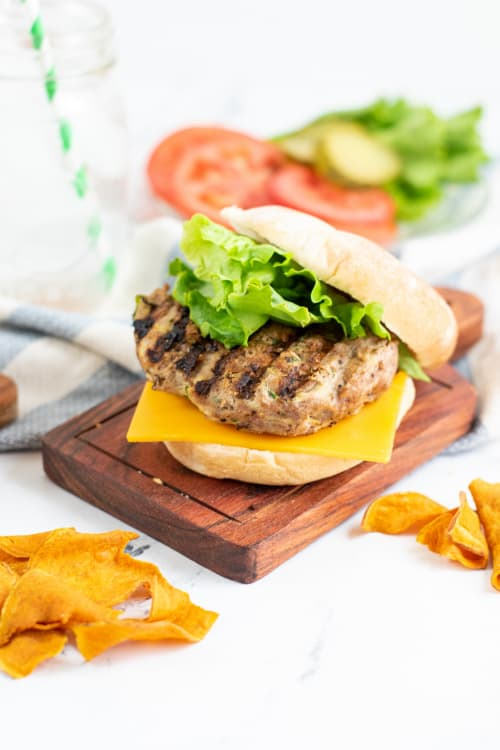 A turkey zucchini burger on a wooden platter topped with lettuce