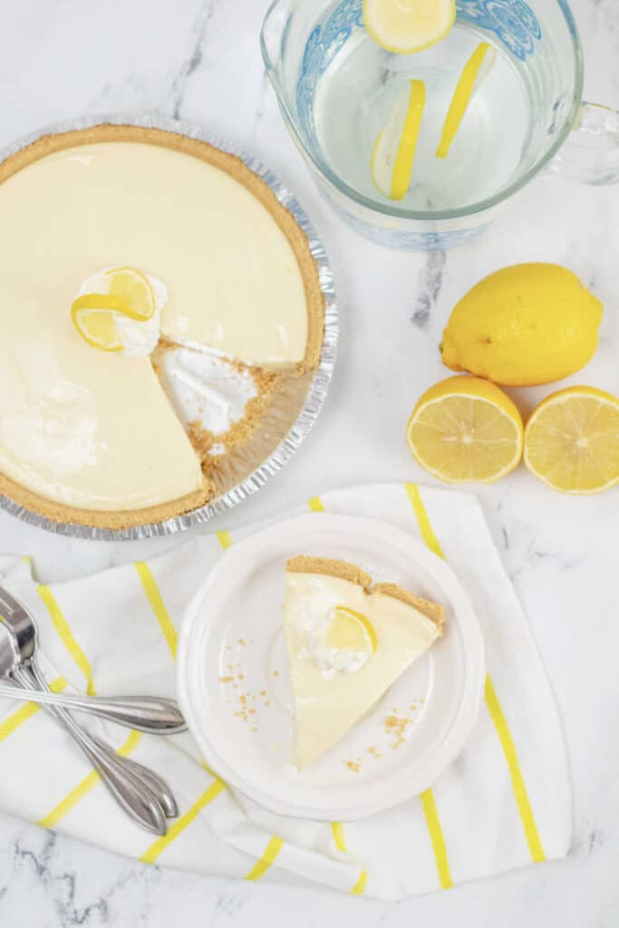 A lemon pie with a piece cut out, a slice of pie is next to it on a white plate