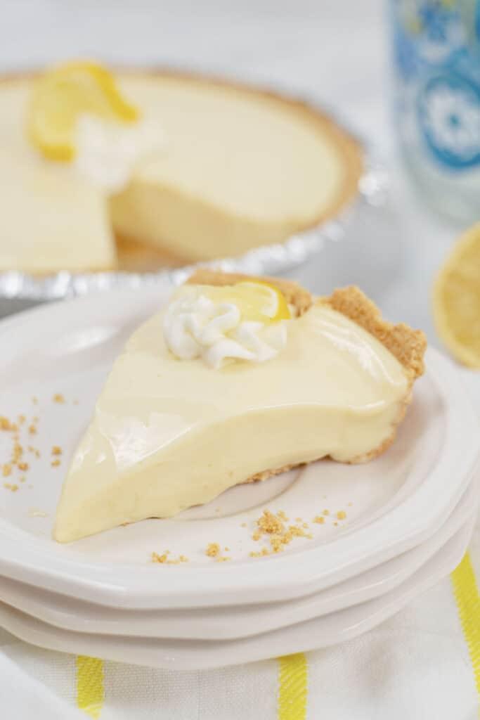 A slice of lemon ice box pie on a white plate