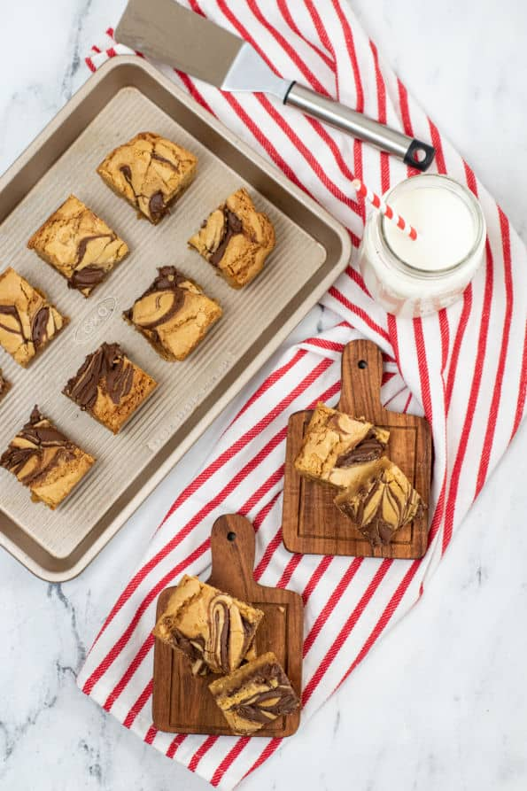 Cut up Nutella blondies displayed on a baking sheet and wooden plates.