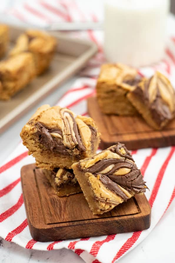 A stack of Nutella swirl blondies on a small wooden chopping block.