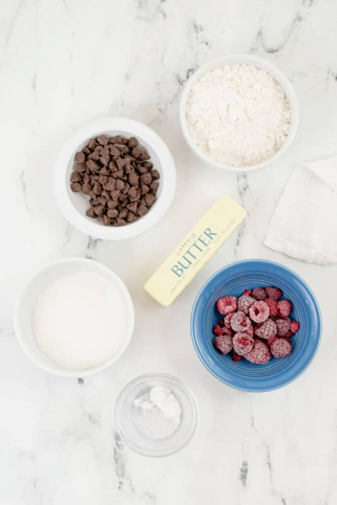 the ingredients for raspberry cookies on a marble counter top.