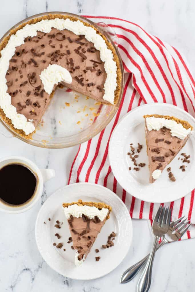 A chocolate pie with slices missing from it. In front of it are 2 white plates each with a slice of pie on them. There is a red and white linen and a white cup of coffee.