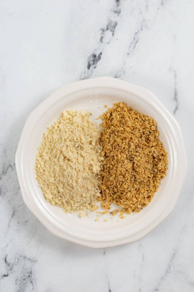 A small white plate with almond flour on it. To the left is raw flour and to the right is golden brown toasted flour