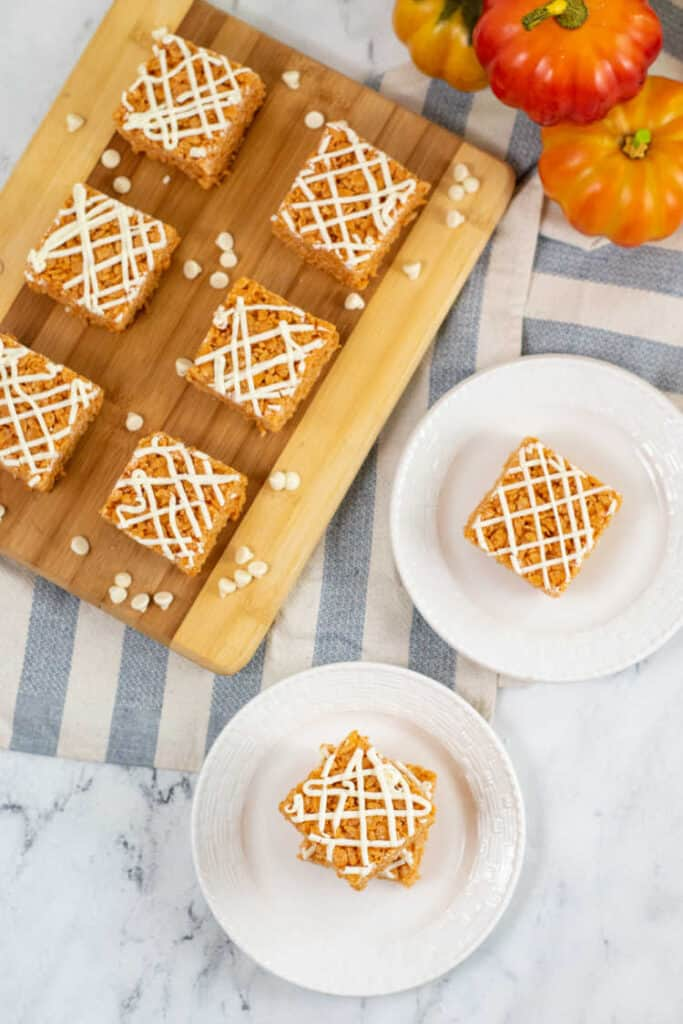 Two white plates each with a pumpkin spice rice krispie treat on top. A wooden board with rice krispie treats arranged on it and a stack of pumpkins