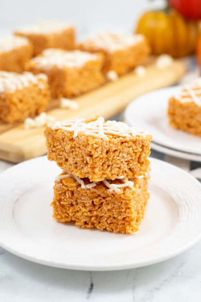 A white plate with a stack of two pumpkin spice rice krispie treats on it.