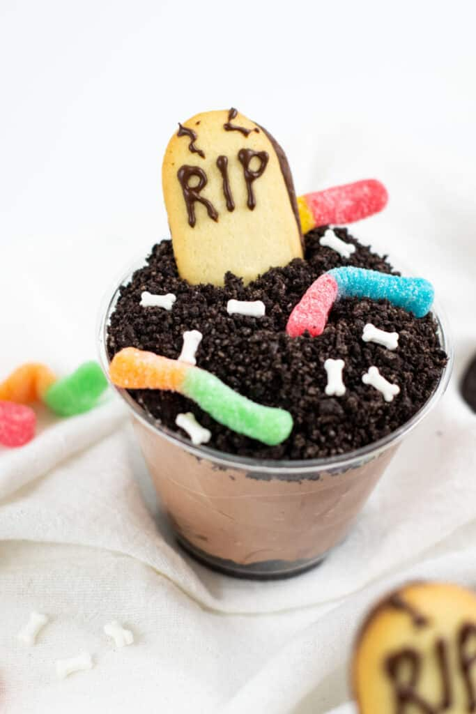 A Halloween dirt cup with gummy worms and a Milano cookie tombstone that says RIP.
