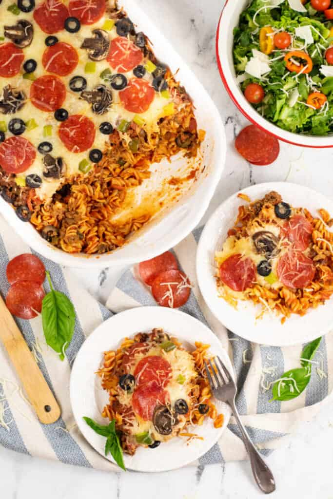 A table with a pizza casserole in a dish, two plates with servings of pizza casserole and utensils
