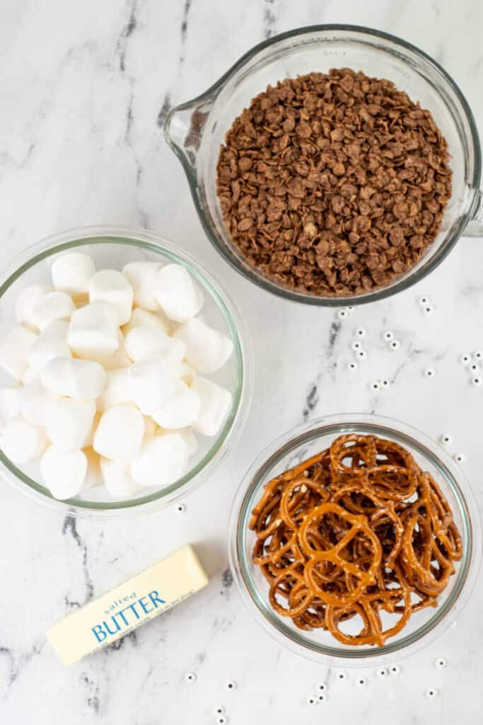 The ingredients for spider treats on a marble counter top. Cocoa krispies, marshmallows, pretzels, butter, candy eyes
