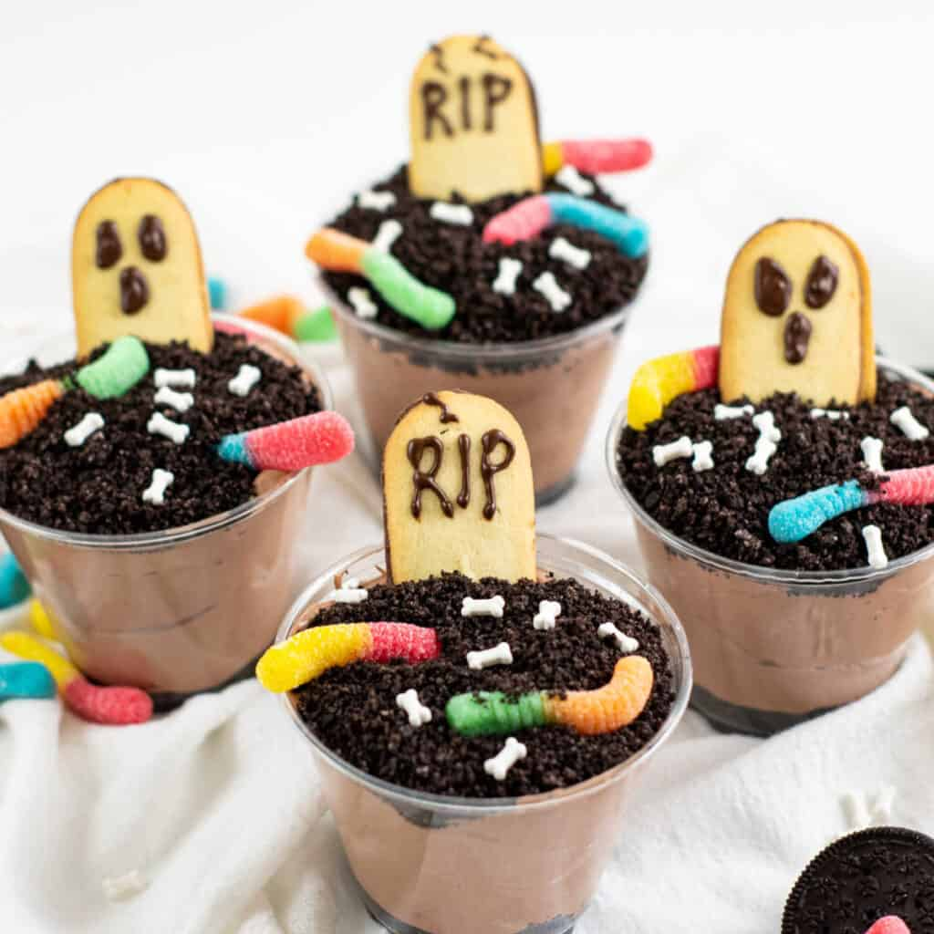 Four halloween pudding dirt cups on a white table cloth.