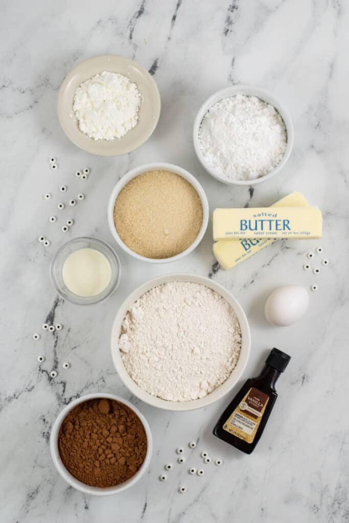 A marble countertop with cookie ingredients spread out on it.