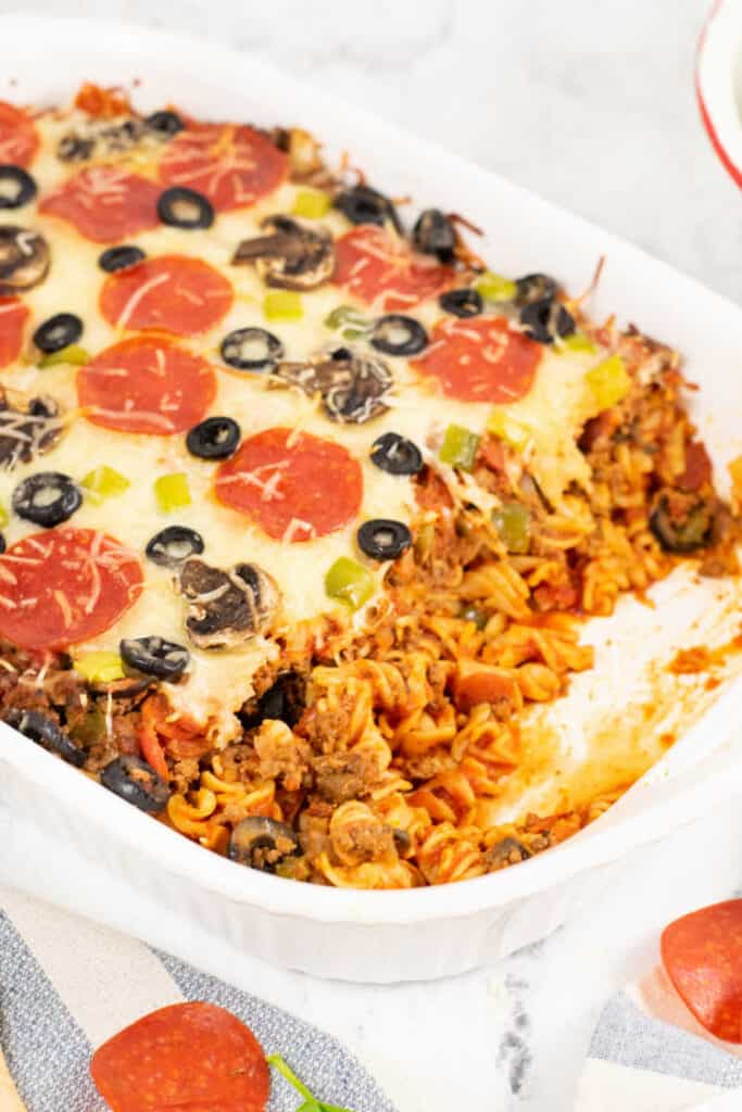 A white casserole dish filled with pizza pasta