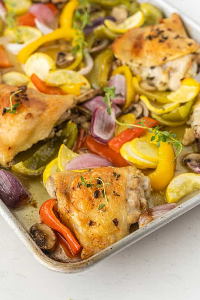 a baking sheet with roasted chicken and vegetables.