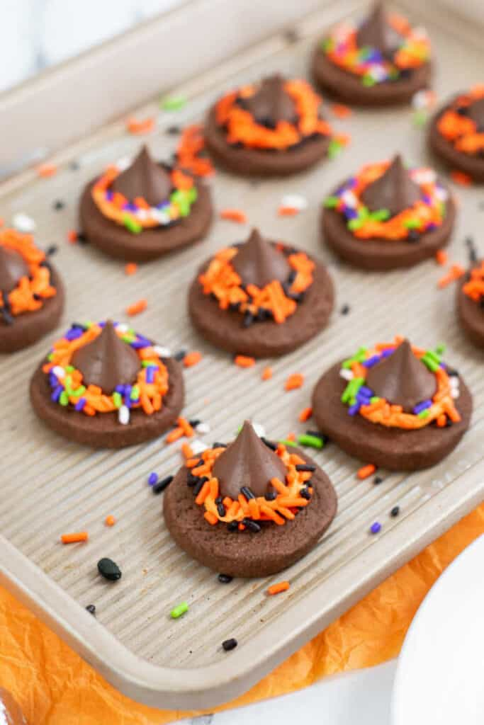 a metal cookie sheet with rows of witch hat cookies on it.