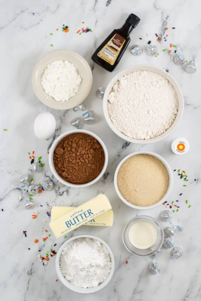 The ingredients for making witch hat cookies. Vanilla, corn starch, flour, egg, cocoa powder, sugar, cream, butter, powdered sugar, orange food coloring, Hershey's Kisses, and sprinkles